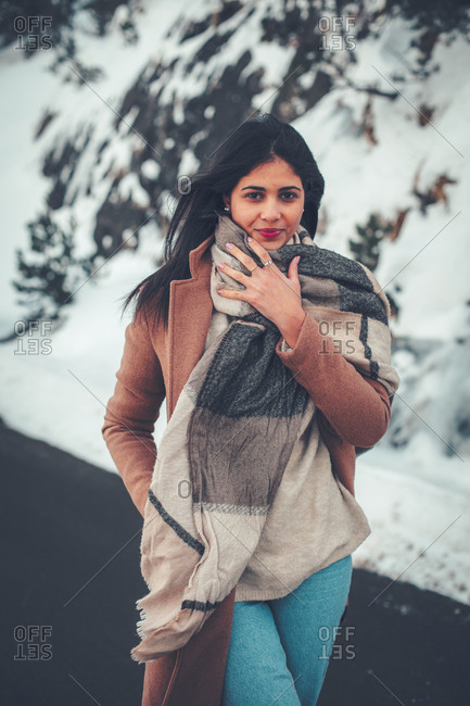 Young woman with dark hair wearing large scarf in winter