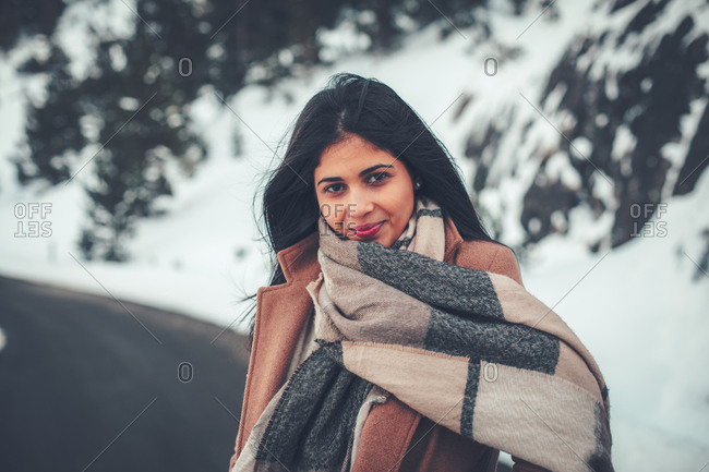 Portrait of a young woman with dark hair wearing large scarf in winter