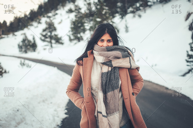 Young woman with dark hair bundled in thick scarf on rural road in winter