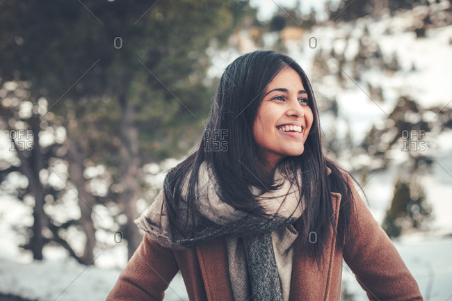 Portrait of a smiling young woman with dark hair outdoors in winter