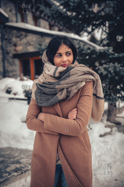 Young woman with dark hair walking outdoors in winter