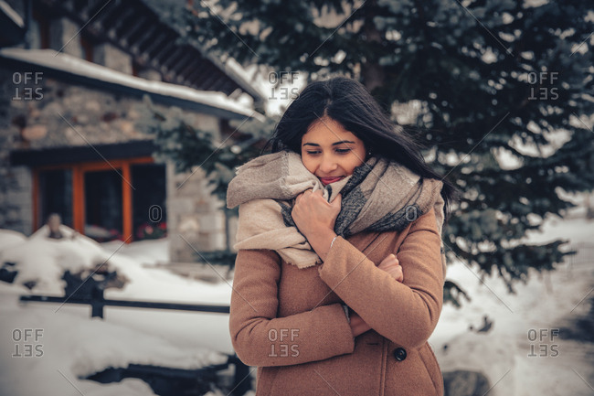 Young woman with dark hair bundled up while walking outdoors in winter