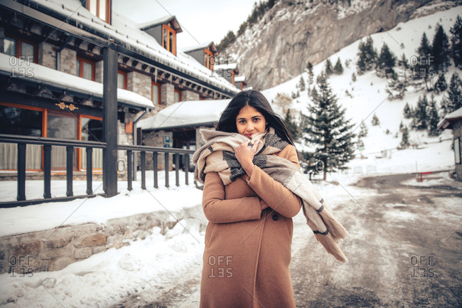 Beautiful young woman with dark hair walking in town in winter