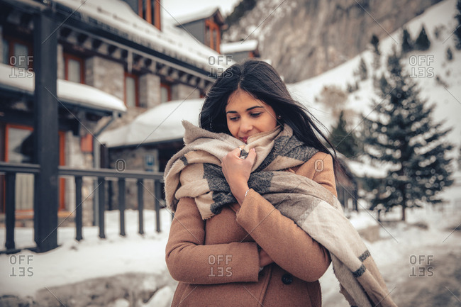 Young woman with dark hair walking outside in town in winter