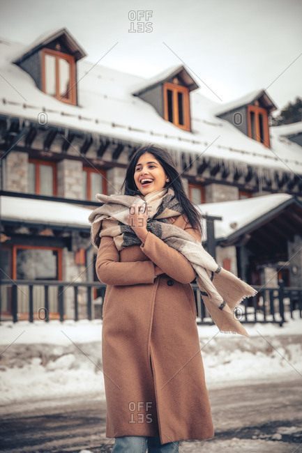 Beautiful young woman with dark hair laughing while outdoors in town in winter