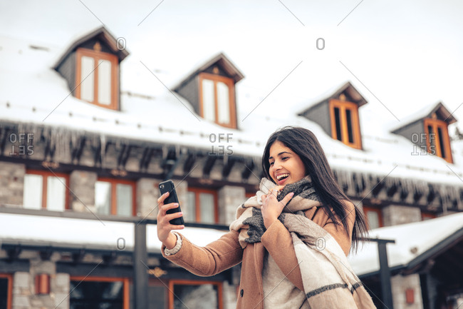 Young woman with dark hair taking selfie with cell phone outdoors in winter
