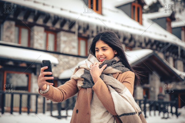 Young woman with dark hair laughing while video chatting on phone outdoors in winter