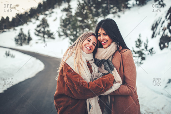 Two beautiful young women standing on rural road in winter