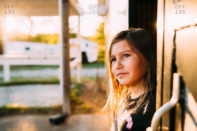 Young girl looking out barn door in golden light