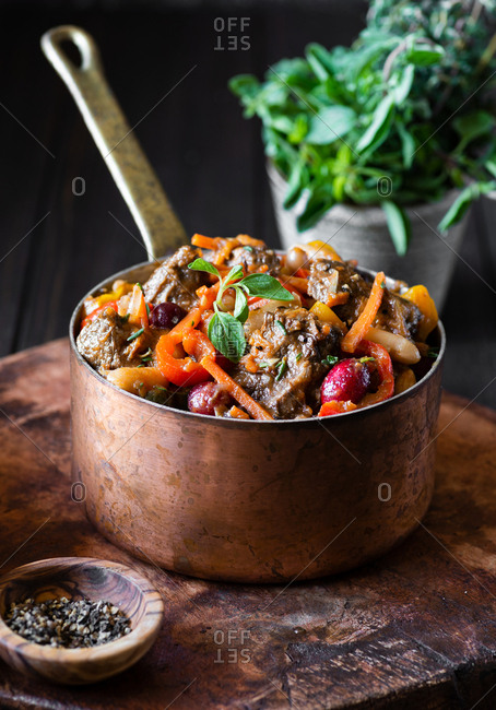 Beef stew with carrot, peppers, beans and cranberries in vintage copper pot