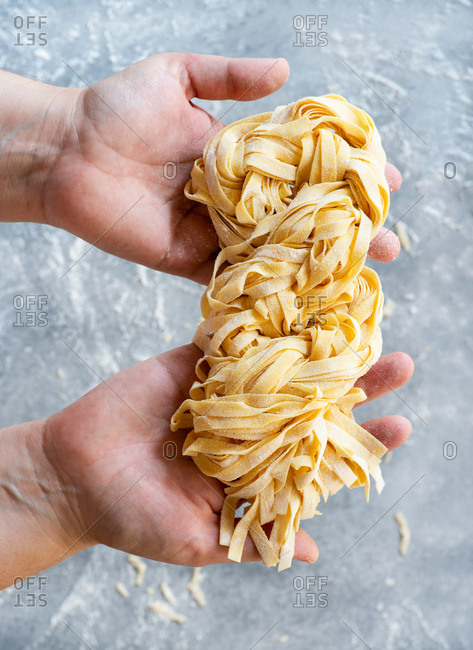 Fresh egg pasta in the palm of hands from above