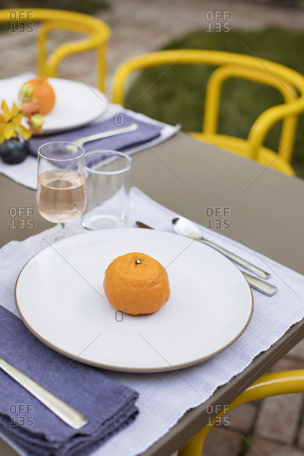 A single orange on a plate beside wine on an outdoor table