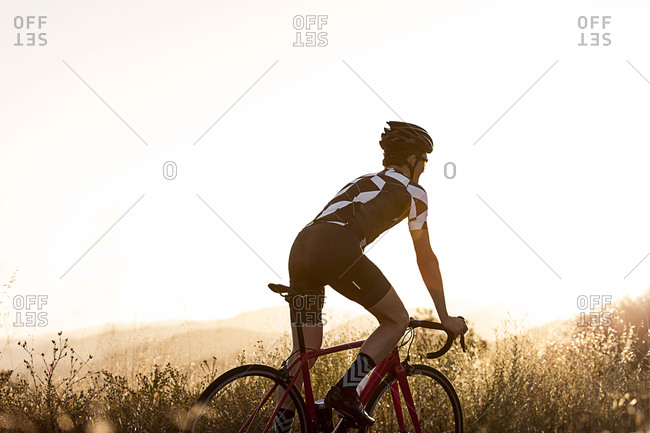 Side view of young man cycling against clear sky during sunny day