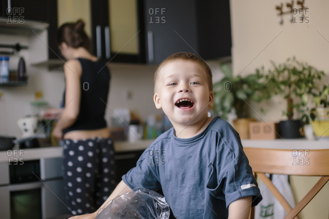 Portrait of happy boy with mother working in background at home