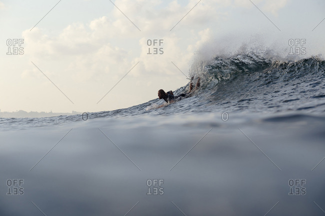 Man surfboarding on waves in sea against sky during sunset