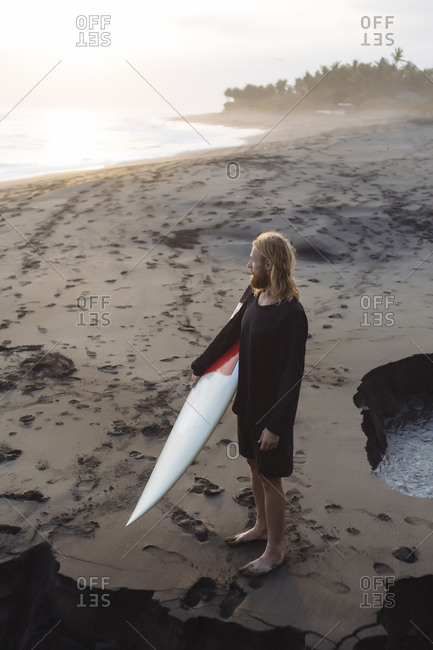 Full length of man looking away while carrying surfboard at beach