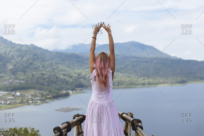 Rear view of woman with arms raised standing at observation point against cloudy sky