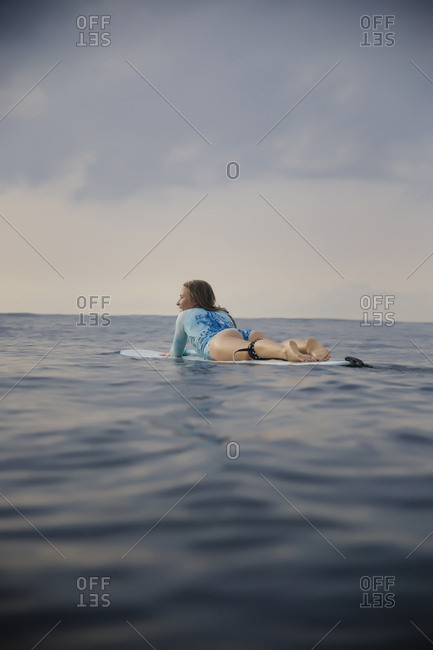Full length of carefree woman lying on surfboard in sea against sky