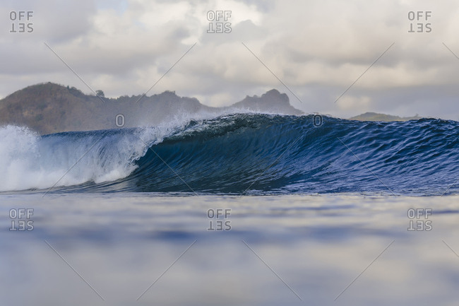 Scenic view of waves against cloudy sky