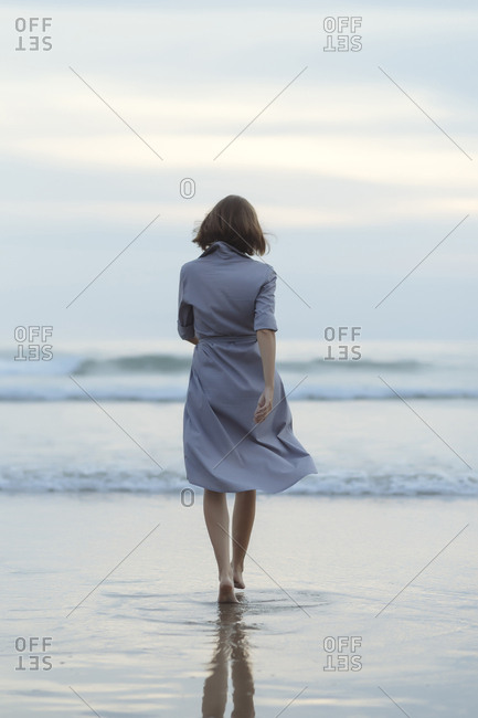 Rear view of carefree woman walking towards sea on shore at beach during sunset