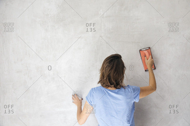 Rear view of woman sanding wall with hand sander