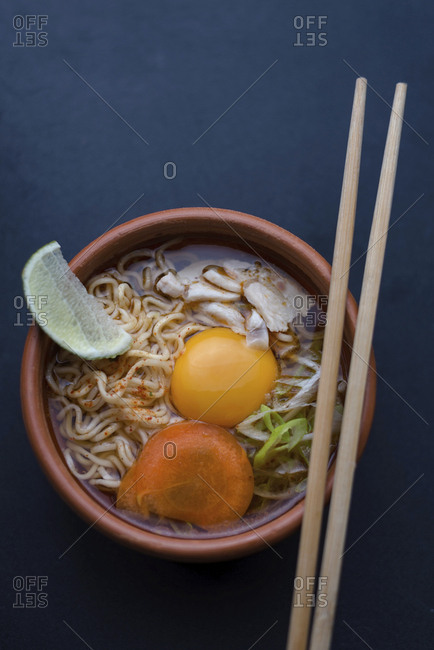 Overhead view of instant noodles soup served in bowl with chopsticks on table