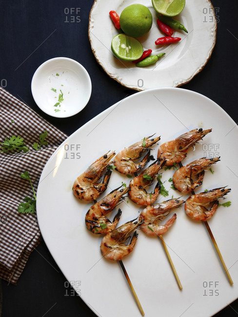 Overhead view of roasted shrimps in skewers on plate