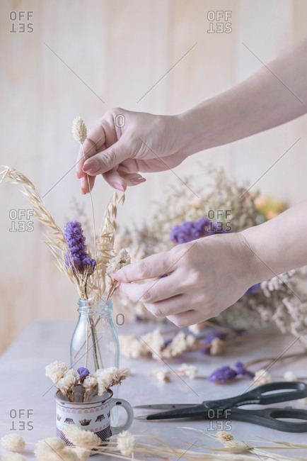Cropped hand of woman arranges dried flower into glasses bottle