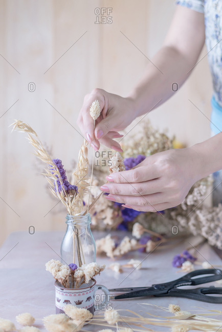Cropped hand of woman arranges dried flower into vase