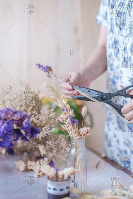 Cropped hand of florist trimming the flower stem