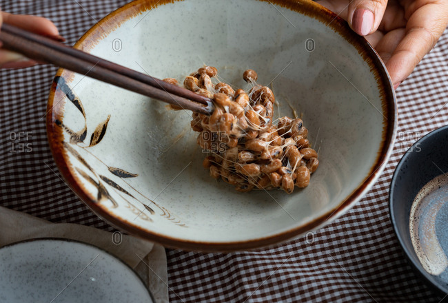 Cropped hand of woman mix a natto in bowl by chopsticks