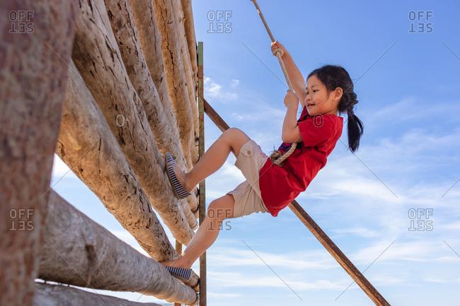 A girl is climbing an adventure toy.
