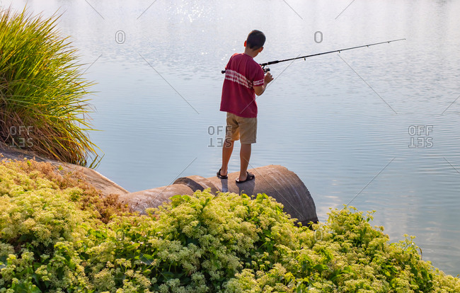 Boy is stand and fishing on culvert