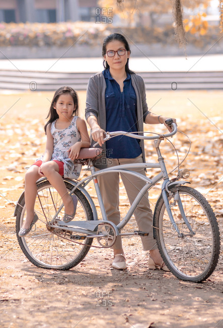 Mother and daughter with flat tires bicycle