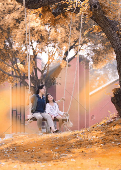 Mother and daughter sit on a swing under the big tree