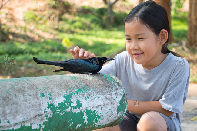 Girl stroking black bird