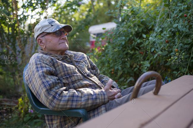 Senior man wearing cap resting in backyard