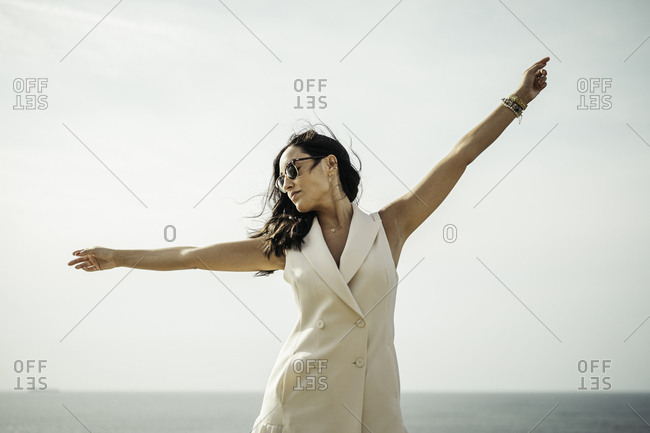 An extended arms young woman with a white dress with a sea horizon in the background