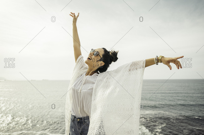 A happy young woman with extended arms with a sea horizon at the background