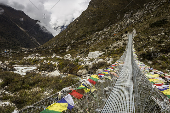 Mountain valley with prayer flag lined swing bridge