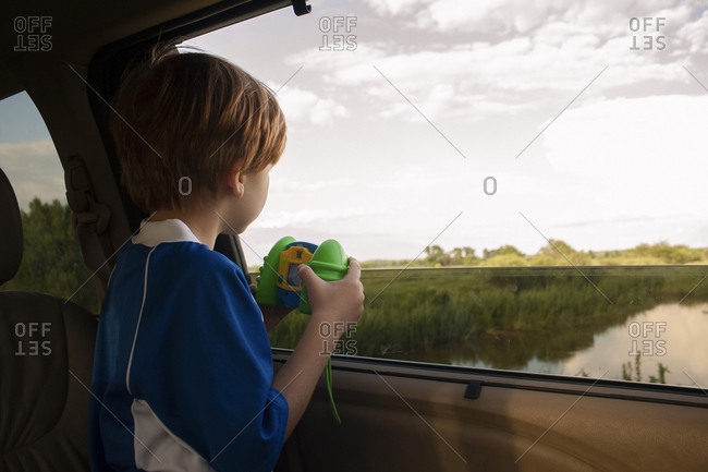 Boy looking at view while holding toy in car