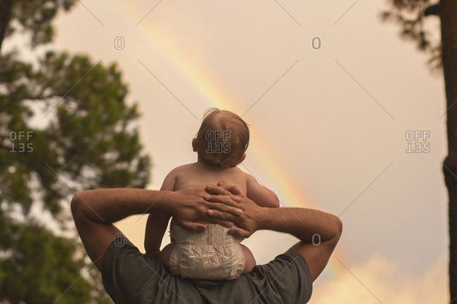 Rear view father carrying son on shoulders while looking at rainbow