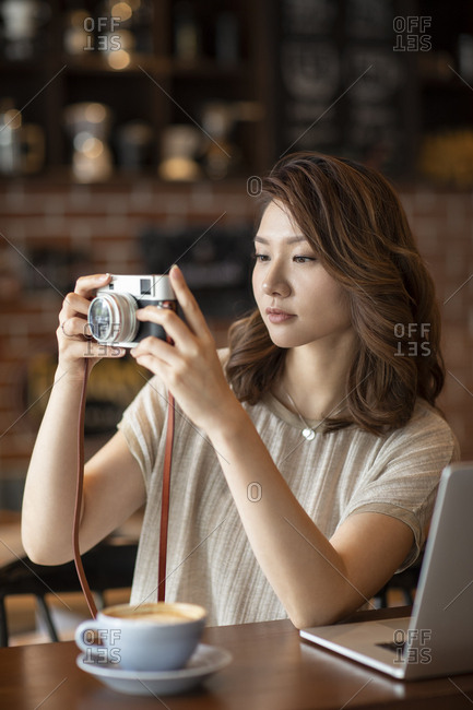 Elegant Chinese woman using digital camera in cafe