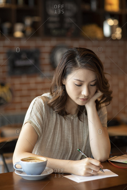 Elegant Chinese woman writing postcard in cafe