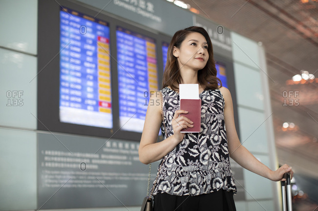 Chinese businesswoman with passport and airplane ticket in airport