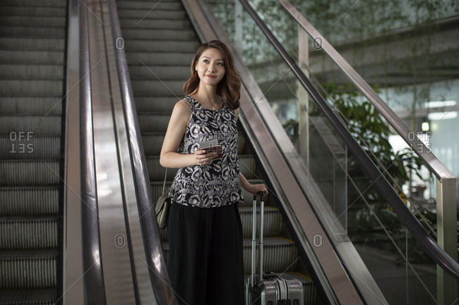 Chinese businesswoman with luggage in airport