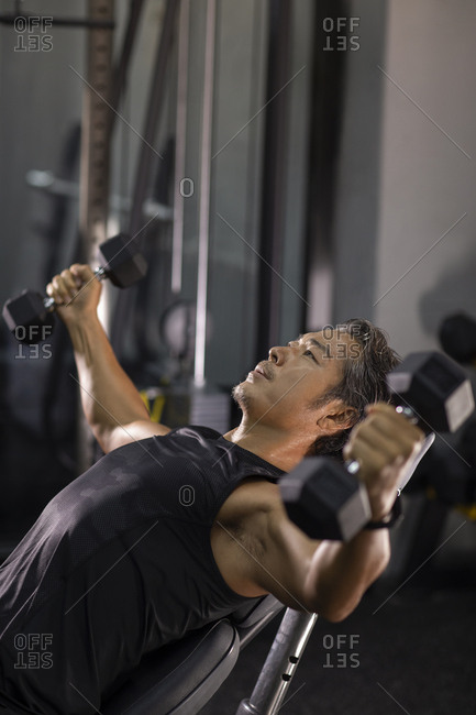 Mature Chinese man working out with hand weights at gym