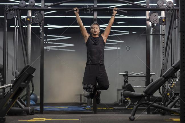 Mature Chinese man exercising at gym