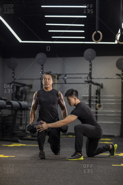 Mature Chinese man working out with personal trainer at gym