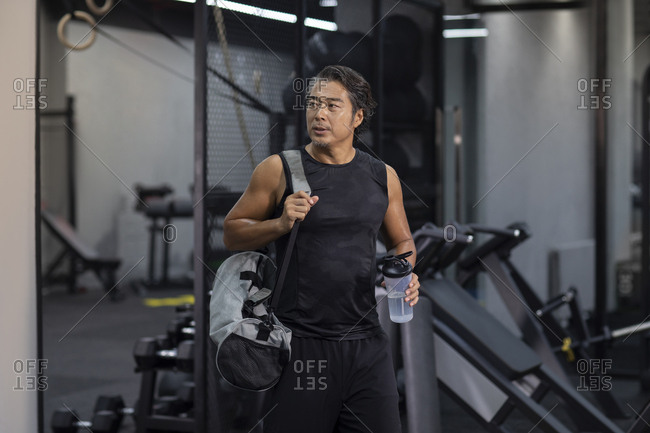 Mature Chinese man with gym bag at gym
